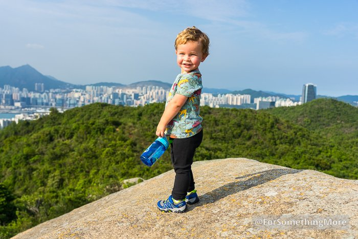 toddler standing on large boulder