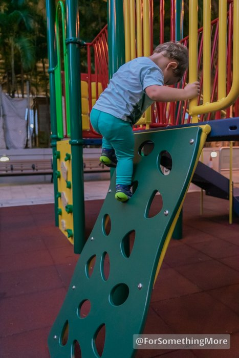 Toddler using Merrell Bare Steps Ridge Jr shoes while climbing on a playground
