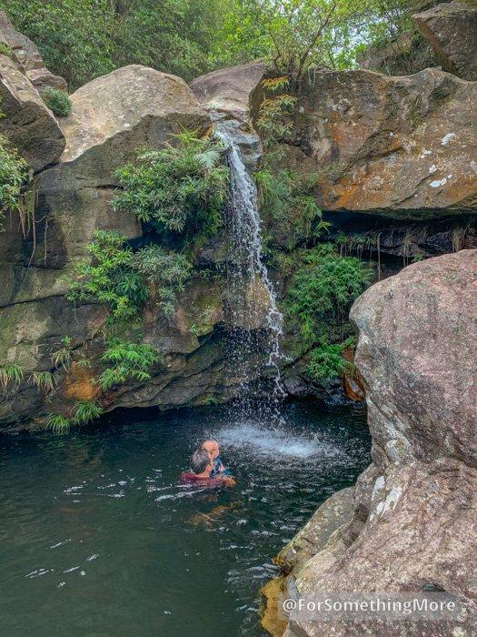man swimming in waterfall at Ping Nam Stream