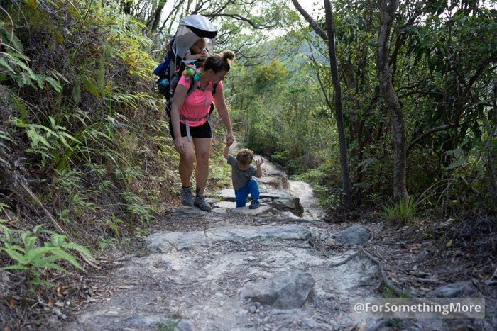 woman hiking with toddler and baby